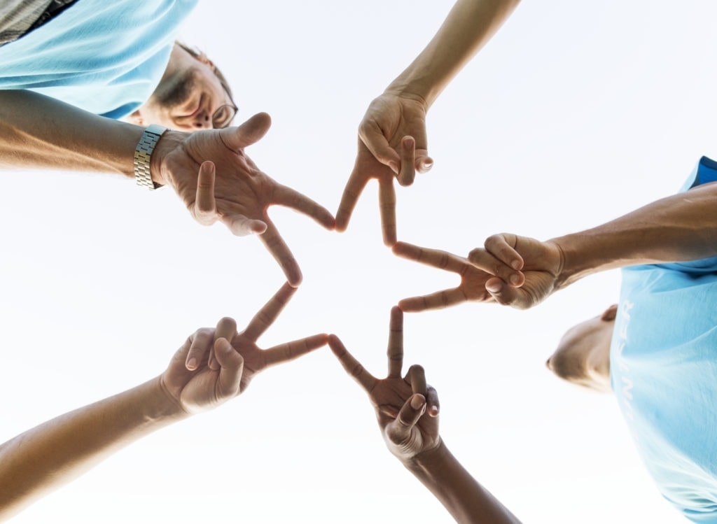 People using their hands to form a star